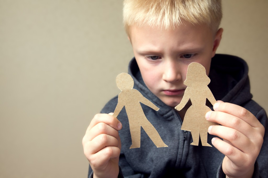 Child with cut out paper of parents