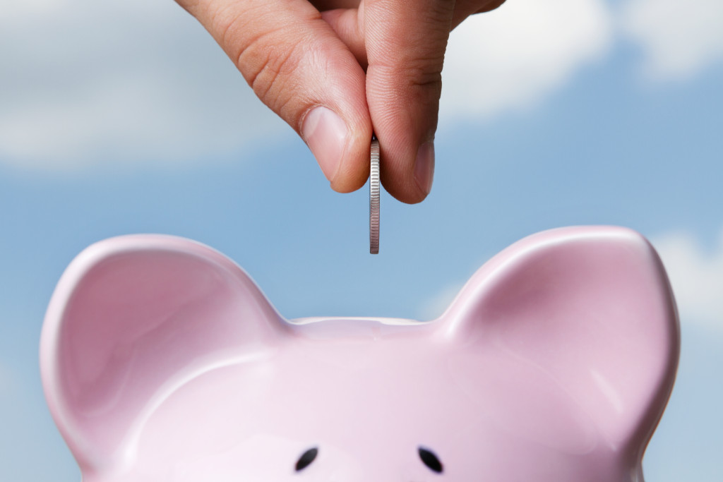 putting a coin into piggy bank